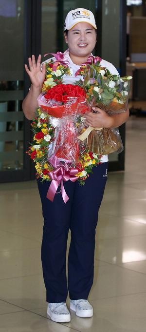 ▲ 박인비가 4일 인천국제공항을 통해 입국, 꽃다발을 들고 손을 흔들고 있다. /연합뉴스