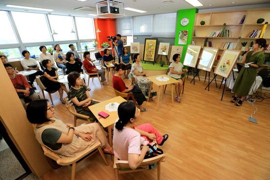 ▲ 과천시여성비전센터 열린마당에서 미니콘서트가 열린 가운데 참석자들이 민화 작품 설명을 듣고 있다.