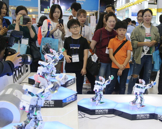 ▲ 13일 고양시 킨텍스 제1전시장에서 개막한 2017로보월드에서 관람객들이 전시용 로봇을 바라 보고 있다.   /연합뉴스
