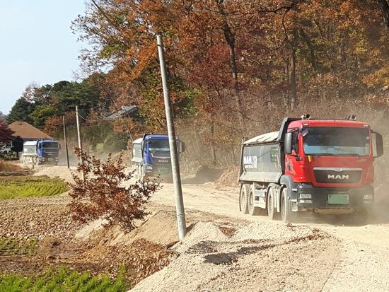 ▲ 김포시가 2월부터 주요 농로구간를 통행하는 대형차량을 집줃단속한다고 밝혔다. 덤프트럭들이 농로를 흙먼지를 날리며 운행하고 있다.  <김포시 제공>