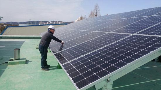 ▲ 구리시 관계자가 하수처리장 건물 옥상에 설치된 태양광 설비를 점검하고 있다. <구리시 제공>