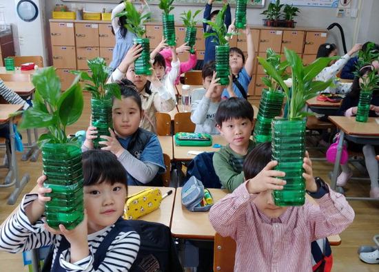 ▲ 화성시 행정초는 미세먼지 대응 및 예방을 위한 'e-맑은숨 안전 프로그램'을 운영한다. 프로그램에 참여한 학생들이 공기정화식물을 들어보이고 있다. <행정초 제공>