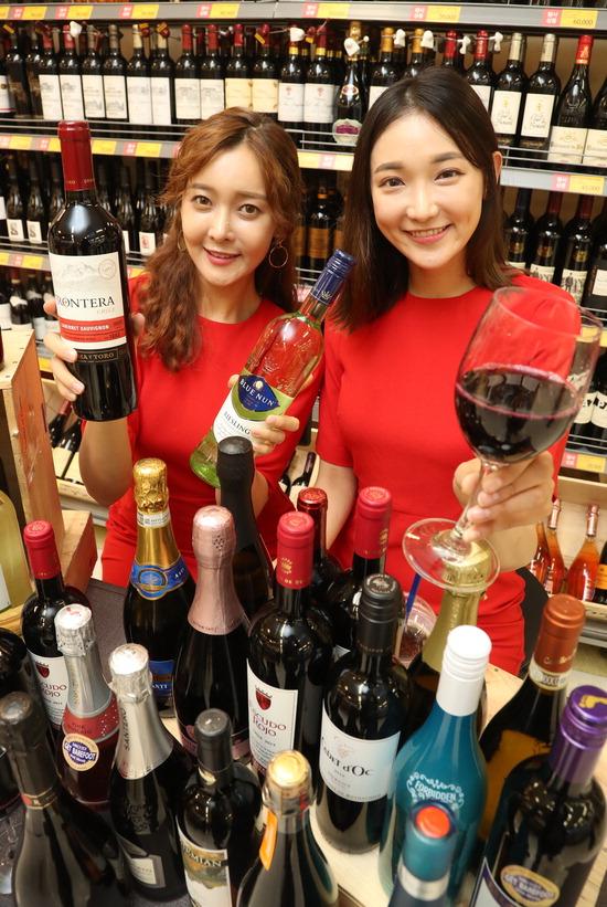 ▲ 국내 대표 와인 행사로 자리 잡은 이마트 '와인장터'가 열린 17일 오전 서울 이마트 용산점에서 모델들이 와인을 소개하고 있다. 20일까지 열리는 이번 장터에서는 와인 800여 품목을 최대 80%까지 할인한다.  /연합뉴스