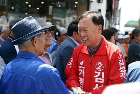 ▲ 자유한국당 김성기 가평군수 후보가 가평읍 장날을 찾은 군민들과 인사를 나누고 있다.