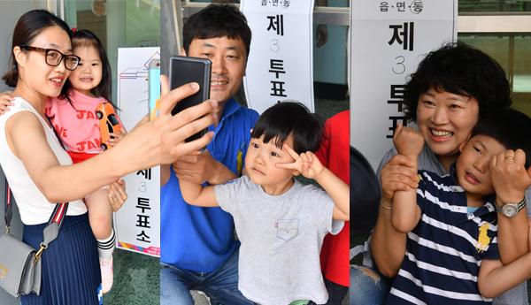 ▲ 13일 인천시 남동구 구월중학교에 설치된 투표소에서 투표를 마친 부모들이 함께 온 자녀들과 투표 인증샷을 찍고 있다.  이진우 기자 ljw@kihoilbo.co.kr