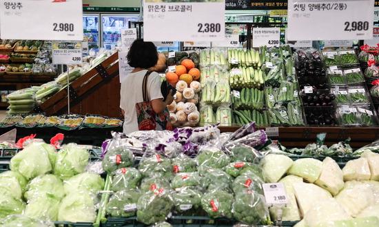 ▲ 21일 오후 서울의 한 마트 채소 코너에서 한 시민이 폭염으로 성큼 올라버린 야채들의 가격을 확인하며 물건을 고르고 있다. .  /연합뉴스<br /><br />