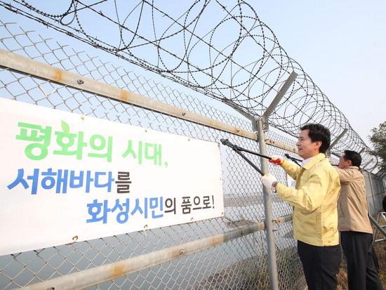 ▲ 서철모 화성시장과 김홍성 시의회 의장이 서해안 군사 철조망을 제거하고 있다. <화성시 제공>