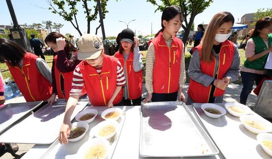▲ 수원여자대학교 사회봉사단 소속 학생들이 2일 오후 수원시 권선구 평동 은하수공원에서 열린 경로잔치에서 급식봉사를 하고 있다.  홍승남 기자