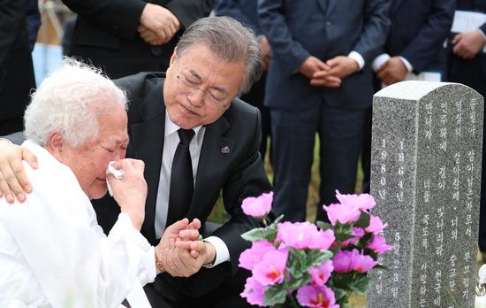 ▲ 문재인 대통령이 18일 광주 국립 5·18민주묘지 희생자 안종필의 묘역에서 어머니 이정임 씨를 위로하고 있다.