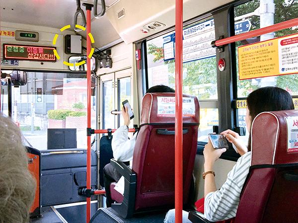 ▲ 지난 16일 인천 간선 2번 버스의 내부 모습. 승차문 위쪽에 와이파이 기기(점선)가 설치돼 있다. 인천시가 이달부터 무료 와이파이 서비스를 제공하고 있지만 시민들은 이를 알지 못한 채 휴대전화를 사용하고 있다.<br /><br />