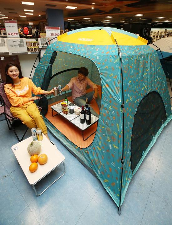 ▲ 28일 오전 서울 이마트 성수점에서 모델들이 할인 행사하는 텐트를 홍보하고 있다. 30일부터 6월 12일까지 빅텐 패밀리 패턴 그늘막(블루, 퍼플 색)'을 이마트 e카드로 결재하면 '30% 할인된 4만8930원에 판매한다. 이외 그늘막, 텐트 제품도 6월 26일까지 e카드로 결재하면 20% 할인을 받을 수 있다.  /연합뉴스