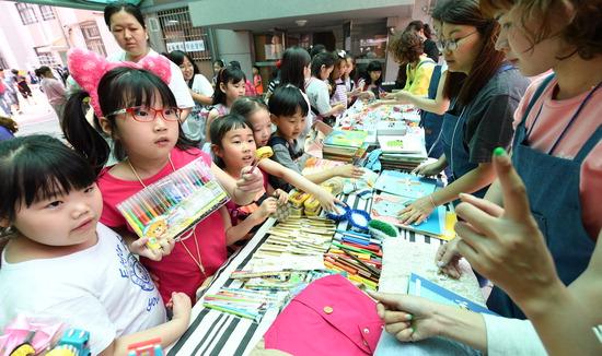 ▲ 수원시 권선구 권선초등학교에서 13일 학생, 학부모, 교직원이 함께 하는 '학교 안 작은장터'가 열려 학생들이 물건을 구매하고 있다. 학부모동아리의 재능기부 물품을 포함한 학생들과 교직원의 기부물품을 판매한다. 수익금은 어려운 학생들을 위해 전액 기부될 예정이다.  홍승남 기자 nam1432@kihoilbo.co.kr