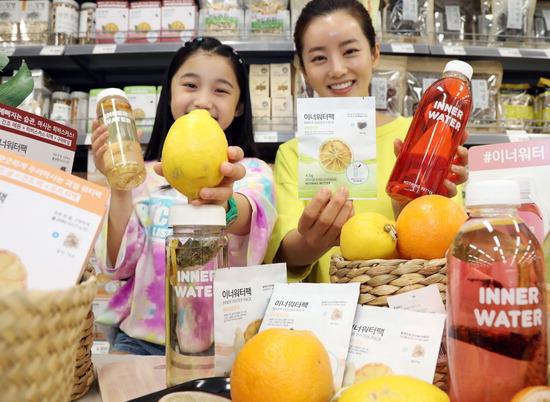 ▲ 17일 오전 이마트 서울 용산점에서 모델들이 마시는 건조과일 '이너워터팩'을 소개하고 있다. '이너워터팩'은 건조과일을 물과 함께 병에 우려 마실 수 있는 수분 충전 제품으로 과일에 함유된 비타민과 미네랄을 그대로 섭취할 수 있다.  <이마트 제공>